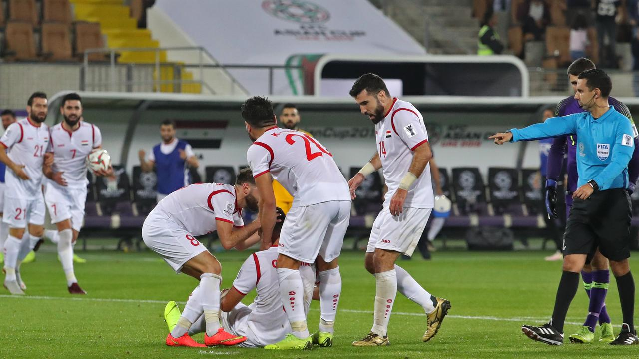 Syria's forward Omar Al-Soma (sitting) is congratulated by teammates after scoring a goal