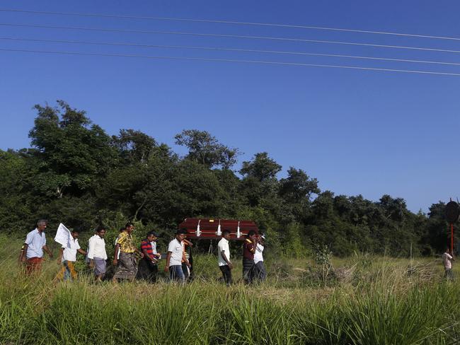 Villagers carry a coffin to a funeral in Padaviya, Sri Lanka. Picture: AP Photo/Eranga Jayawardena.