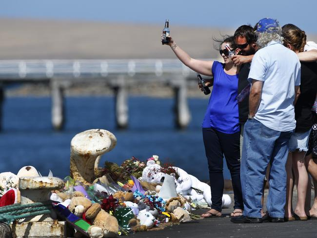Family members of Damien Little raise a toast to Damien and the boys at the scene. Picture: Dean Martin