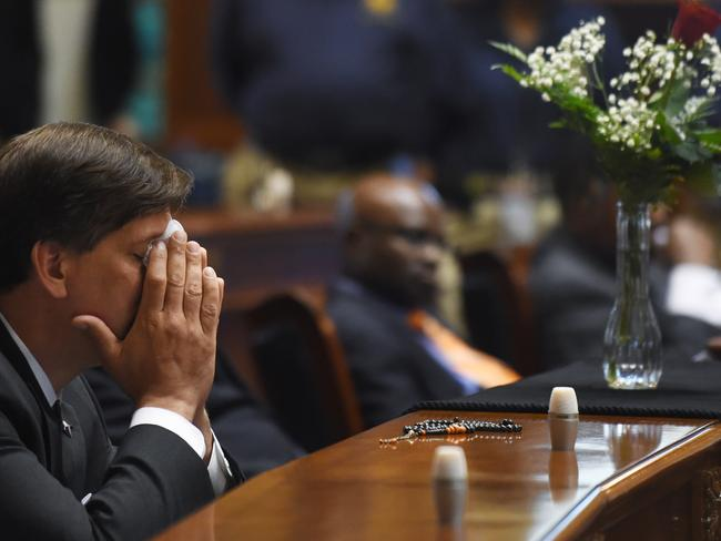 Poignant tribute ... Carolina State Senator Vincent Sheheen gets emotional as he sits next to the draped desk of state Senator Clementa Pinckney on Thursday at the Statehouse in Columbia, South Carolina. Picture: Rainier Ehrhardt/AP