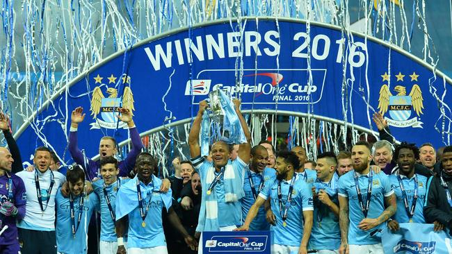 Manchester City's Belgian defender Vincent Kompany (C) holds up the League Cup.