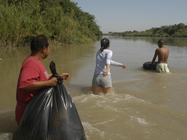 """Harsh conditions ... illegal immigrants wading across the Rio Grande with the help of two """"coyotes"""" or smugglers in an attempt to cross illegally into the United States in Nuevo Laredo, Mexico."""
