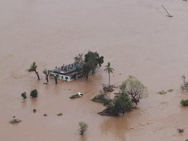 Residents stranded on a roof in Beira, surrounded by deep floods. Picture: Rick Emenaket/Mission Aviation Fellowship/AFP