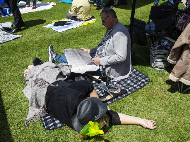 A woman takes a breather as a man studies the race form. Picture: Jenny Evans/Getty Images