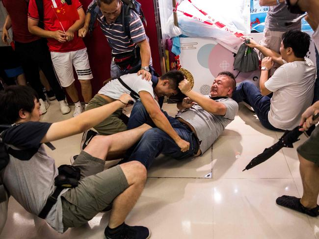 A pro-China supporter (centre R) fights with an anti-government (centre L) protester as others use umbrellas as potential weapons inside a shopping mall. Picture: AFP