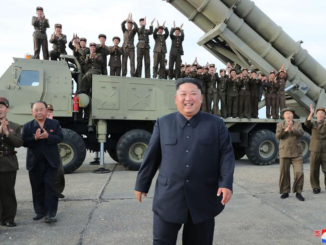 This picture released by North Korea's official Korean Central News Agency shows Kim Jong-un celebrating the test-firing of a 'newly developed super-large multiple rocket launcher'.