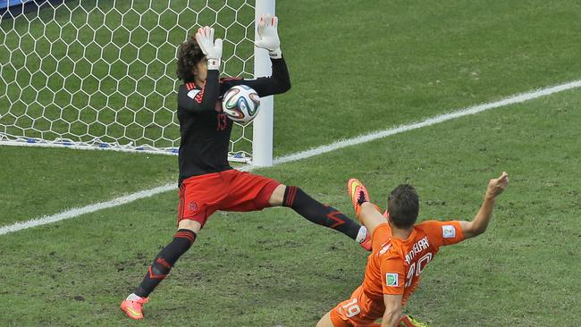 Mexico's goalkeeper Guillermo Ochoa makes from Holland's Klaas-Jan Huntelaar.