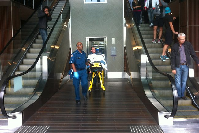 Paramedics wheel one of the victims from a lift at busy Robina Shopping centre after a double shooting. Picture: Greg Stolz