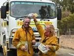 Husband and wife team Marcus and Deb Newlands from Woolsheds CFS cool off after fighting the northern suburbs fire. Picture: Naomi Jellicoe