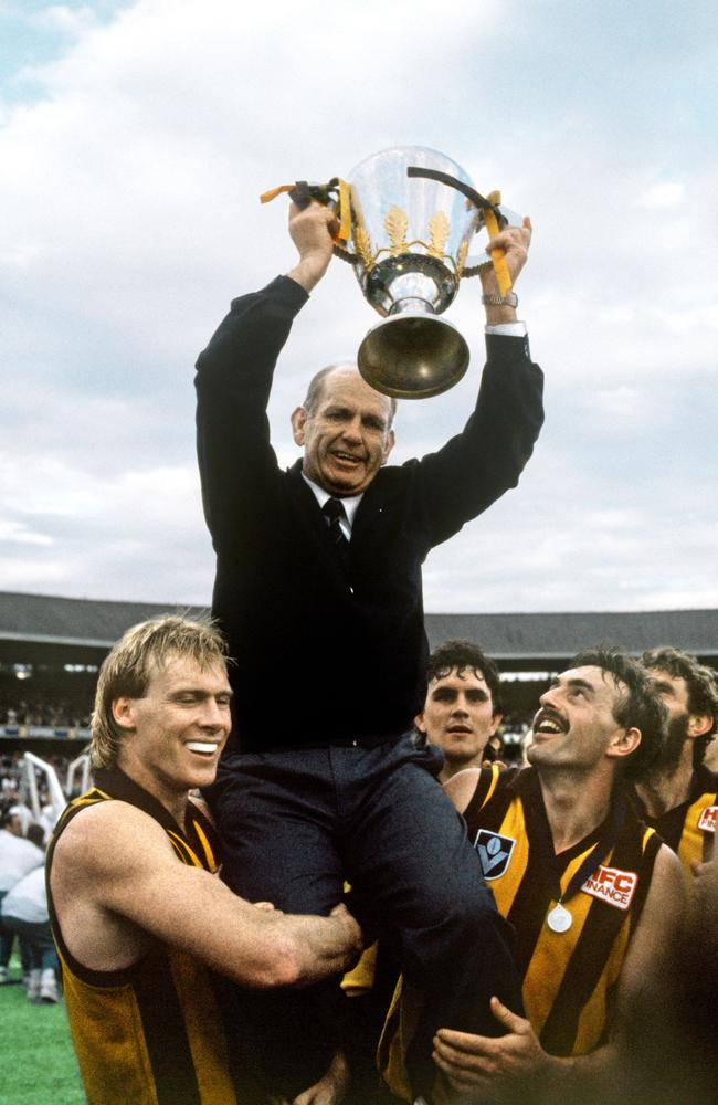 Hawthorn coach Allan Jeans holds up the 1989 premiership cup as Peter Curran and John Kennedy Jr carry the coach off the MCG.