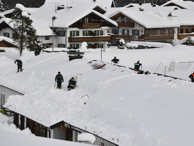 Rescue workers clear a roof following heavy snowfall in the area on January 12, 2019 in Kruen, Germany. Picture: Getty
