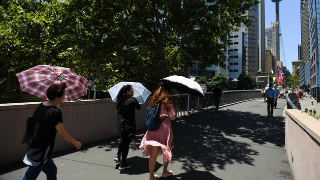 Pedestrians in Sydney CBD trying to stay out of the sun. Heatwave conditions are expected to continue around NSW this weekend, with temperatures set to exceed 40C. Picture: AAP