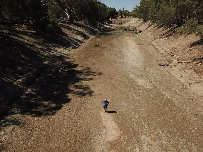 Sheep farmer Wayne Smith stands in the dry river bed of the Darling River on his property near Pooncarie in February 2019. Picture: AAP Image/Dean Lewins