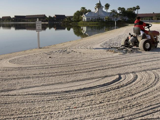 A groundsmen rakes the beaches of Disney's Grand Floridian Resort & Spa at Disney World in Orlando. Picture: AFP