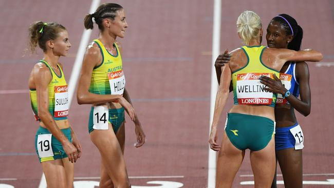 Celia Sullohern, Madeline Hills and Eloise Wellings of Australia congratulate Lineo Chaka of Lesotho after they stayed behind to watch Chaka finish the women's 10000m. Picture: AAP