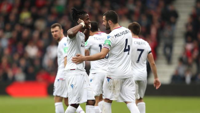 Wilfried Zaha of Crystal Palace celebrates with teammate Luka Milivojevic
