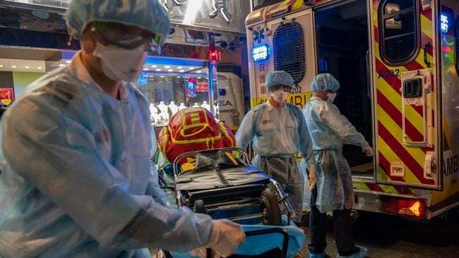 Paramedics wearing personal protective equipment carry a stretcher off an ambulance at North Point district in Hong Kong, China. Picture: Anthony Kwan/Getty Images