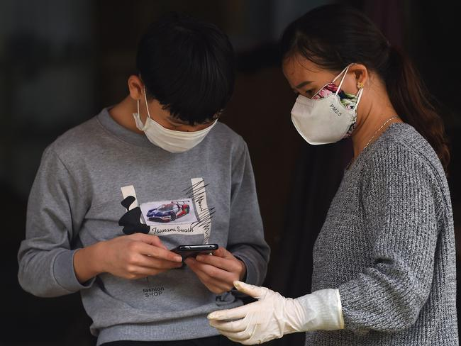 Residents in a quarantined area wearing protective face masks amid concerns the virus is airborne. Picture: Minh Nguyen/AFP.
