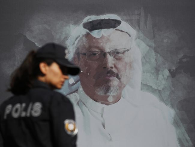 A Turkish police officer with a picture of Saudi journalist Jamal Khashoggi, near the Saudi Arabia consulate in Istanbul, on the one-year anniversary of his murder. Picture: AP Photo