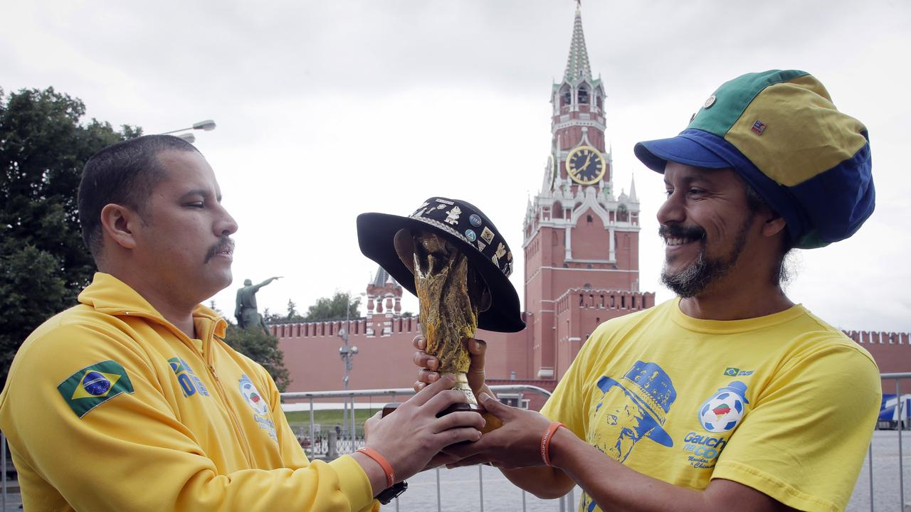 Brazilian fans hold a copy of the World Cup trophy near the Kremlin in Moscow.