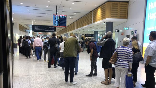Passengers queue at Sydney Airport during the storm.