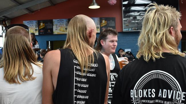 Men wait to be judged on their mullet hairstyles at Mulletfest. Picture: Peter Parks.