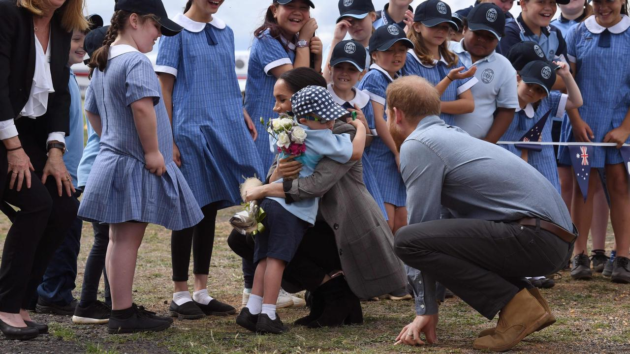 Prince Harry (R) looks on as his wife Meghan, the Duchess of Sussex, is hugged by student Luke Vincent of Buninyong Public School following the couple's arrival at Dubbo Regional Airport in Dubbo on October 17, 2018. Picture: AFP