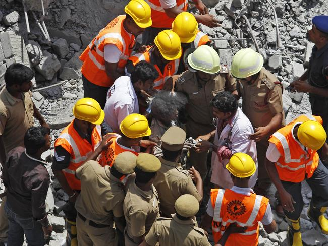 Survivor ... a doctor checks the pulse of a woman worker who was pulled out from the rubble of a building that collapsed during monsoon rains on the outskirts of Chennai, India.