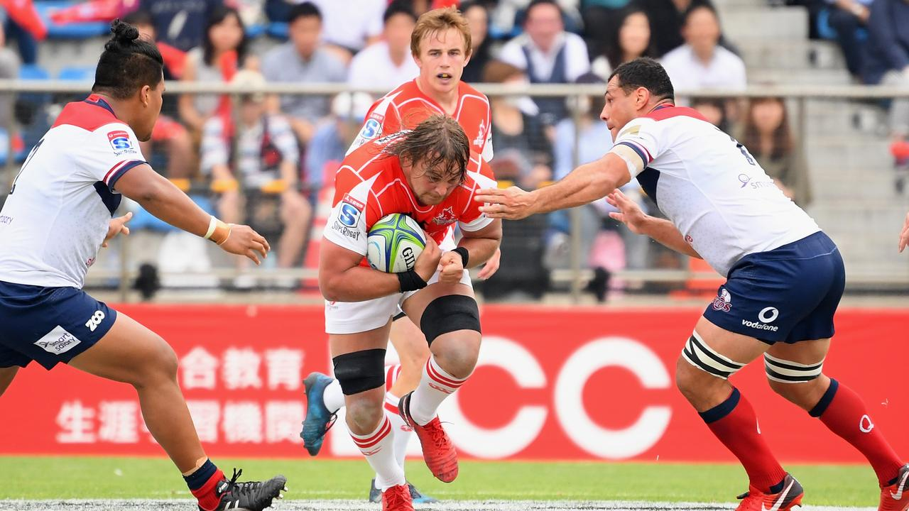The Sunwolves' Wimpie van der Walt of the Sunwolves looks to bust through the defence of the Reds' Brandon Paenga-Amosa (left) and George Smith on Saturday.