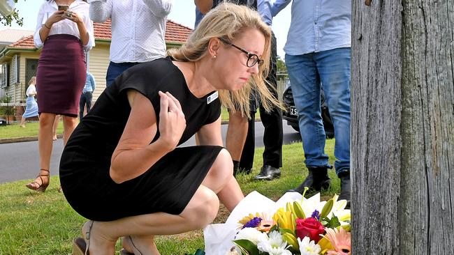 Coorparoo member Fiona Cunningham leaves flowers on Raven Street in Camp Hill. Picture: AAP/John Gass