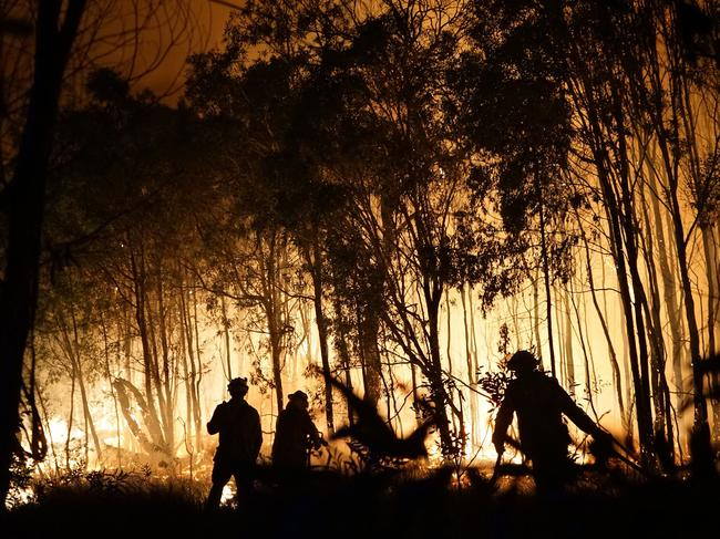 Firefighters battle a blaze on Fingerfield road at the Deepwater National Park area of Queensland. Picture: Rob Griffith/AFP