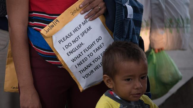 A woman holds a sign written in English to help her find her way, as Central American migrant families wait to board a bus in Texas. Picture: Loren Elliott / AFP