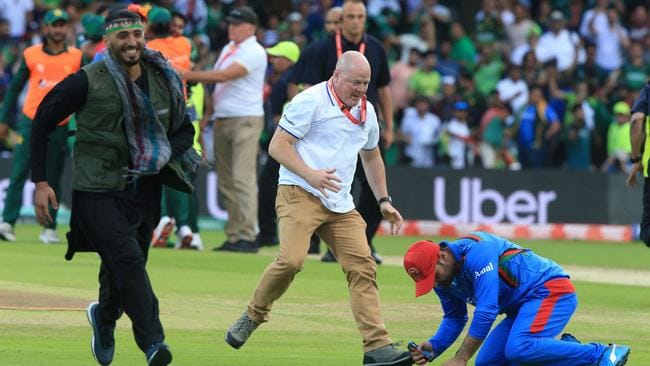 An official (C) assists an Afghan player (R) as a pitch invader (L) runs on the field. Picture: AFP