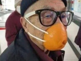 An elderly man sports and orange peel and string mask at Beijing airport. Picture: Weibo