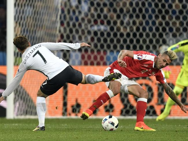 France's Antoine Griezmann, left, and Switzerland's Valon Behrami fight for the ball.
