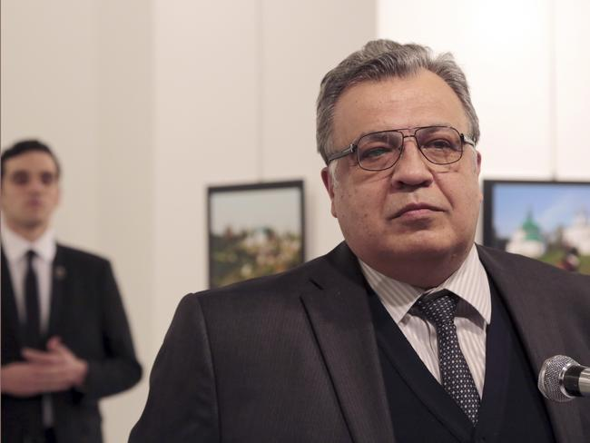 The gunman lurks in the background before shooting Andrei Karlov, the Russian Ambassador to Turkey. Picture: AP Photo/Burhan Ozbilici