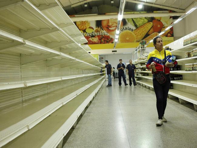 People walk past empty shelves at a supermarket in San Cristobal, Venezuela. Picture: Carlos Eduardo Ramirez