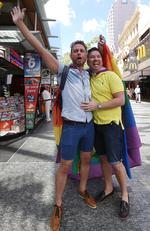 Brad Harker and partner Scott D'Amico walk through the Brisbane mall after the decision. Same-sex couples and their friends and family gather at Queens Gardens this morning to watch the SSM result announced live by the ABS. Pic Peter Wallis