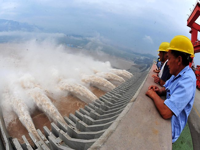 Workers watched as water was released from the dam. Picture: AFP