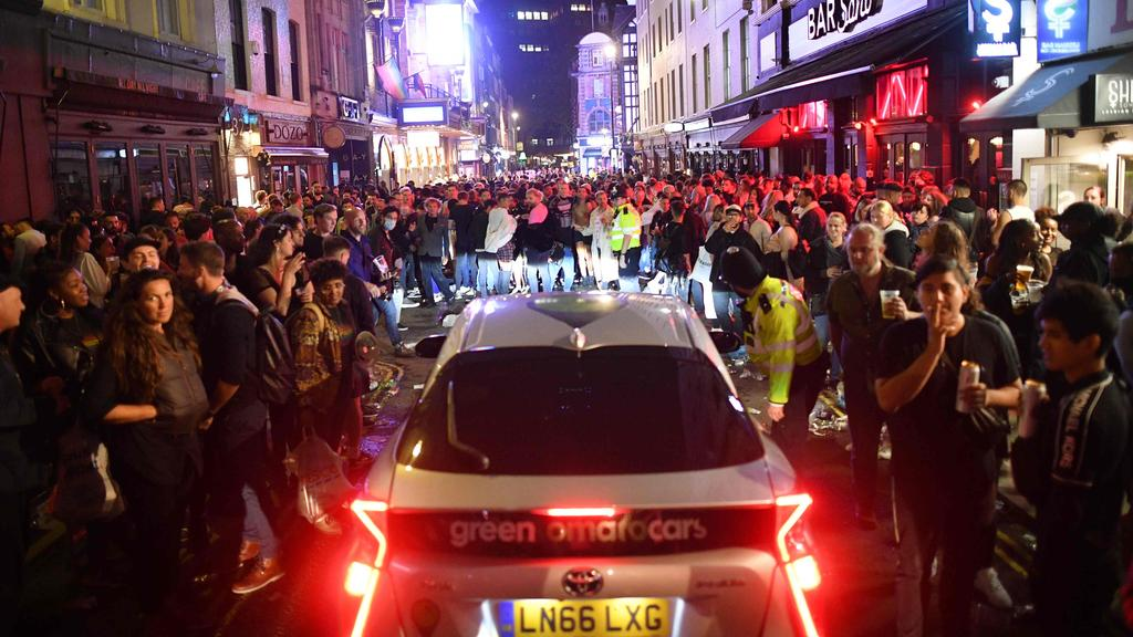 A car tries to drive along a street filled with revellers drinking in the Soho area of London. Picture: AFP