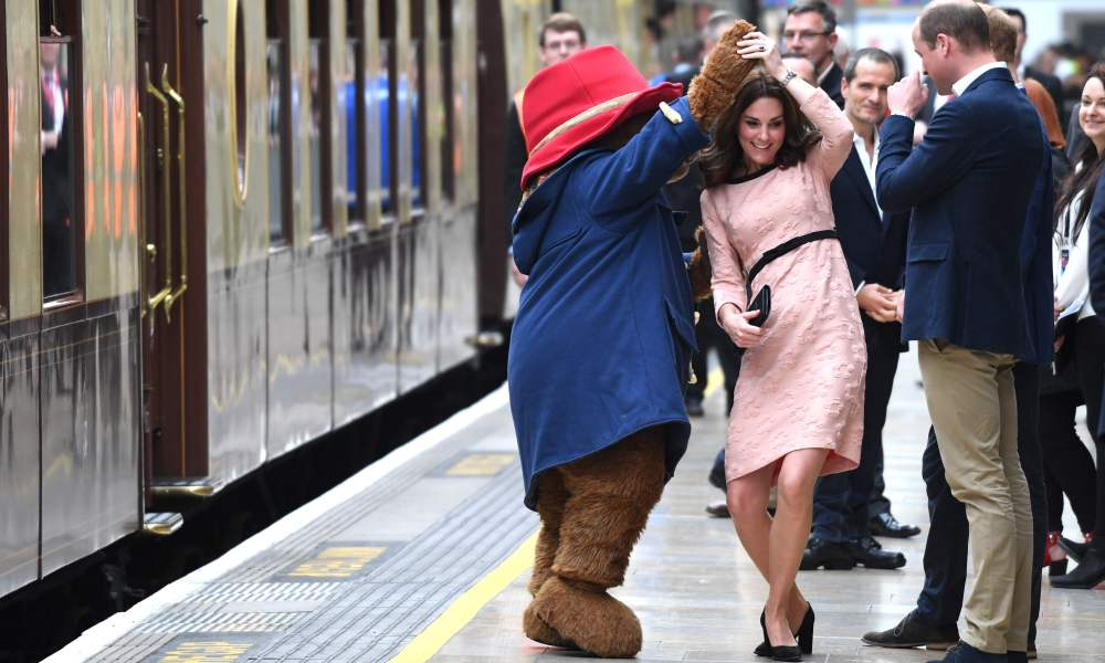 TOPSHOT - Britain's Catherine, Duchess of Cambridge, (C) dances with a person in a Paddington Bear outfit by her husband Britain's Prince William, Duke of Cambridge as they attend a charities forum event at Paddington train station in London on October 16, 2017. / AFP PHOTO / Chris J Ratcliffe