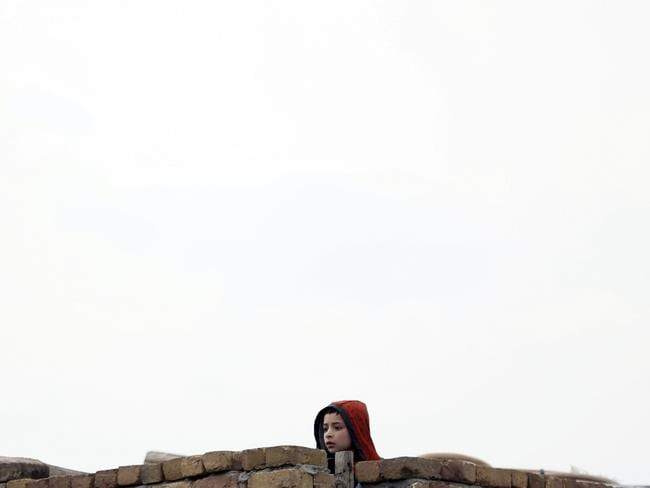 A child watches the site of the attack from a rooftop, in Kabul. Picture: AP