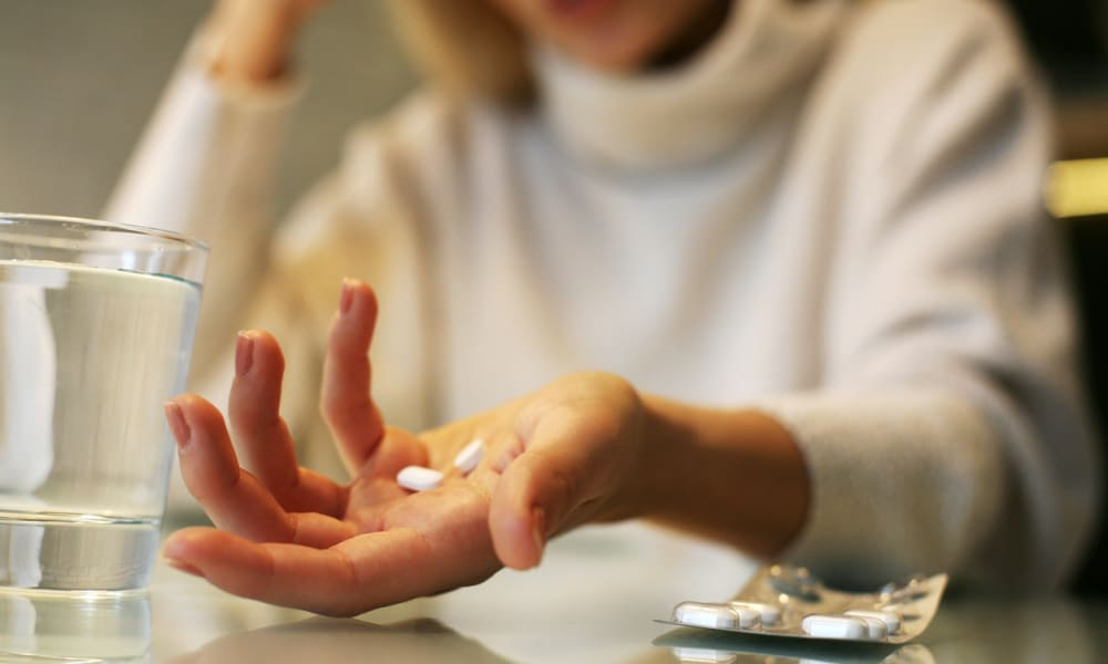 Close up of woman hands holding a pills.