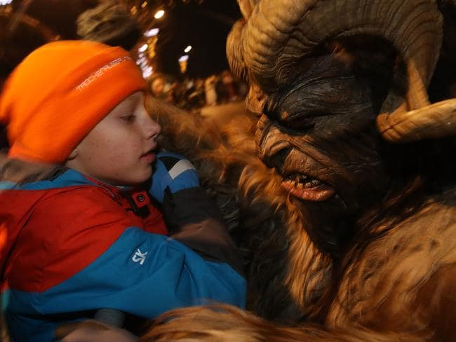 Naughty or nice? A little boy speaks to a devilish Krampus creature during the annual Krampus parade on Saint Nicholas Day on December 6, 2017 in Sankt Johann im Pongau, Austria. Picture: Getty