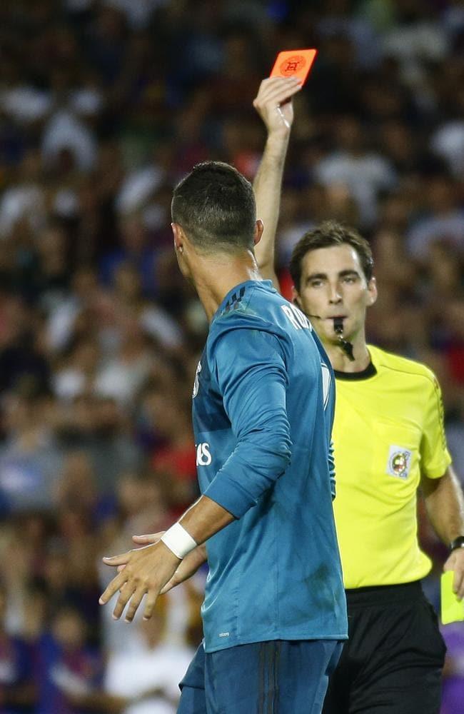 Referee Ricardo de Burgos, right, shows a red card to Real Madrid's Cristiano Ronaldo.