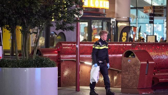 A Dutch police officer secures a bag with items from the scene of a stabbing incident. Picture: AP/Phil Nijhuis