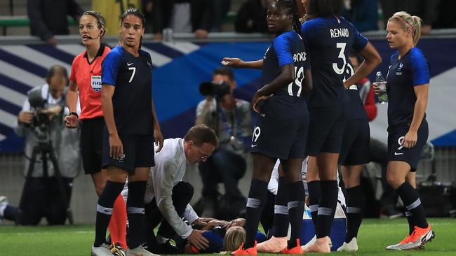 The French players gather around the injured Amandine Henry.