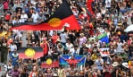 Protestors are seen crossing the Victoria Bridge during the Invasion Day rally in Brisbane, Sunday, January 26, 2020. Thousands of people joined rallies across Australia in support of Aboriginal and Torres Strait Islanders who are calling for an end to the celebration of Australia Day on January 26, which commemorates the arrival of the First Fleet to Sydney in 1788. (AAP Image/Darren England) NO ARCHIVING