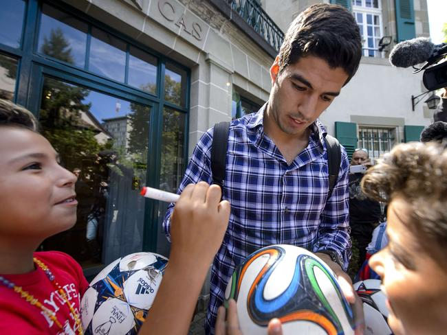 Barcelona's Uruguayan forward Luis Suarez is surrounded by fans after he pleaded his case before the Court of Arbitration for Sport.
