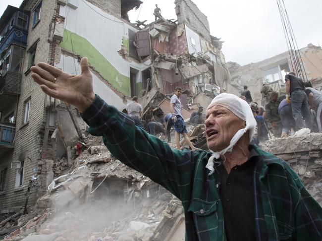 Crime or confusion ... Igor Chernetsov, whose wife was killed in a building demolished by an air strike, gestures near the collapsed structure in Snizhne, 100 kilometres east of Donetsk, eastern Ukraine.